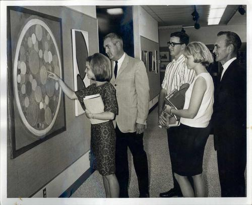 Black and white photograph of people in 1960s clothes pointing at an abstract painting of circles.